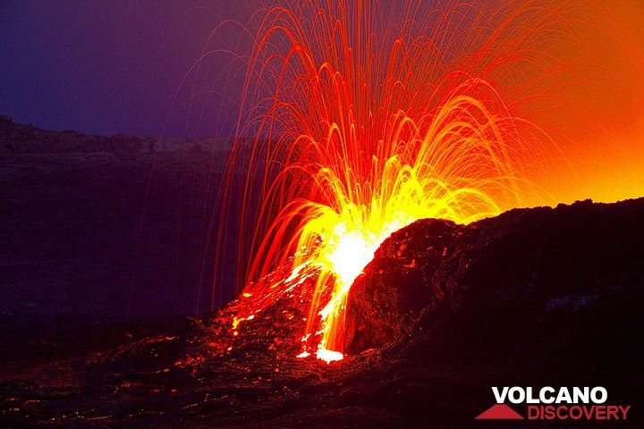 Exploding lava bursts from the lava lake of Erta Ale volcano, seen in the morning twilight. Lava is thrown and pushed outside through a breach in the wall containing the lava lake. (Photo: Tom Pfeiffer)