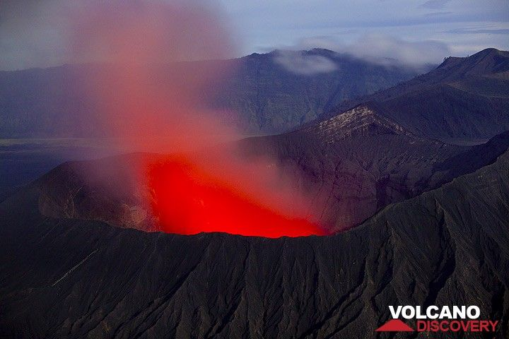 The glowing vent(s) illuminate the diffuse steam and ash plume above Bromo's crater bright red at night. (Photo: Tom Pfeiffer)