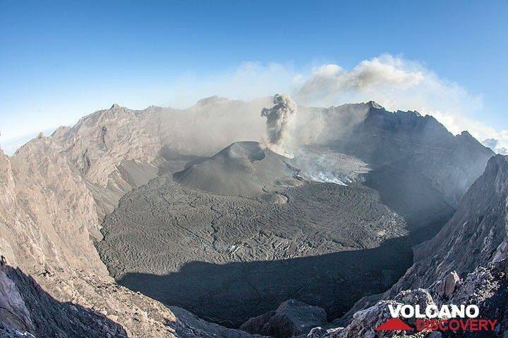 View of the immense, 2 km wide summit crater, a small caldera surrounded by steep walls 4-500 m deep. It reminds a lot of Nyiragongo. The recent eruption has covered the whole floor with fresh lava and built a large cinder cone in the SE part (view is from the north). (Photo: Tom Pfeiffer)
