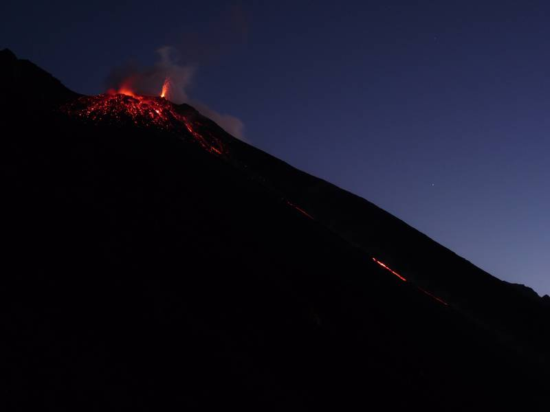 Top part of Stromboli's Sciara del Fuaocco. Droplets of lava illuminating and defining the NE vent right after an explosion, spattering from the NE hornito and glimpse of a thin lava flow from the overflowing/breached larger NE vent. 7 January 2013. (Photo: Ingrid)