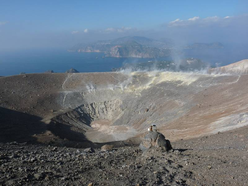 Crater of Vulcano volcano, Lipari in the background and larhe bread crust bomb in the foreground. Italy's Volcanoes: The Grand Tour, October 2013 (Photo: Ingrid)
