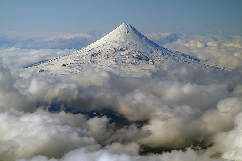 The perfect cone of Shishaldin volcano rises high above a deck of stratocumuls clouds. Pogromni volcano far right. (Photo: marcofulle)