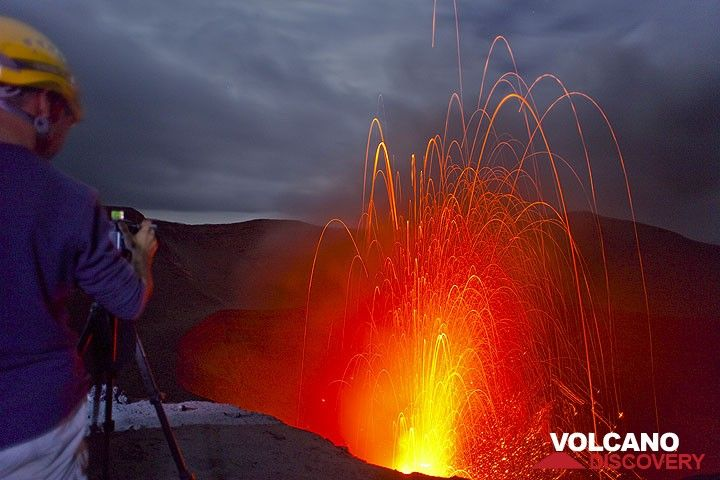 Photographer filming Yasur volcano in the evening. (Photo: Tom Pfeiffer)